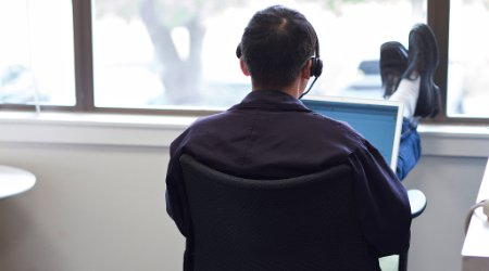 Man listening to podcasts while working on a laptop