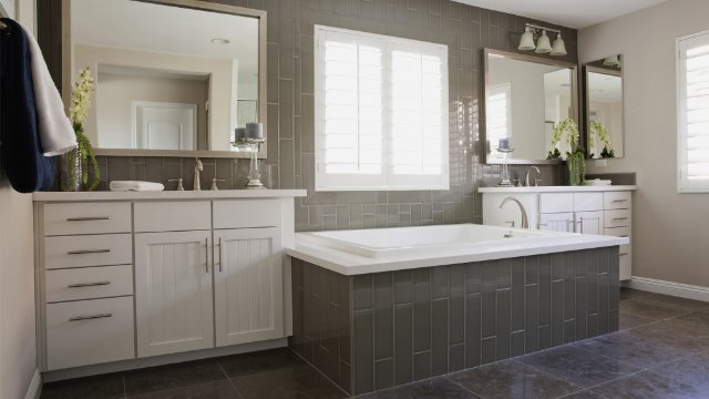 Spacious bathroom with tiled bath and white cabinets at home
