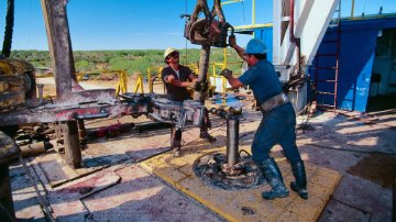 Oil workers assembling a drill