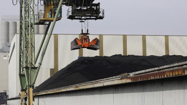 Crane lifting and piling coal in port
