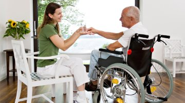Healthcare practitioner giving medicine to a man in a wheelchair