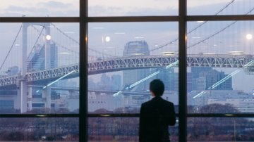 Man looking at Rainbow Bridge in Tokyo