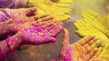 Hands covered in colored dry powder at a Holi spring festival