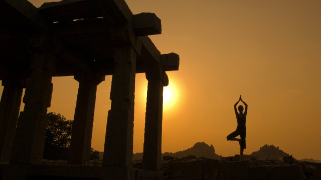 Silhouette of woman doing yoga near temple at sunset