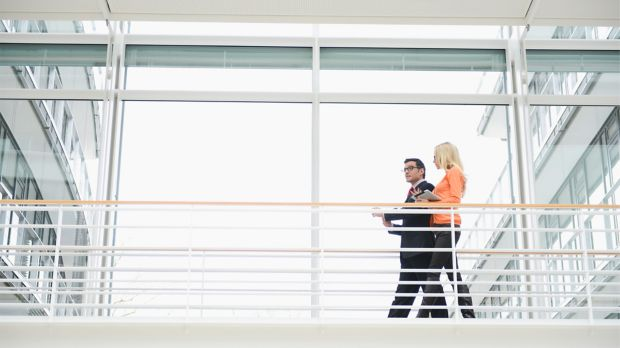 Photo of two business people walking together discussing small and midsize business solutions
