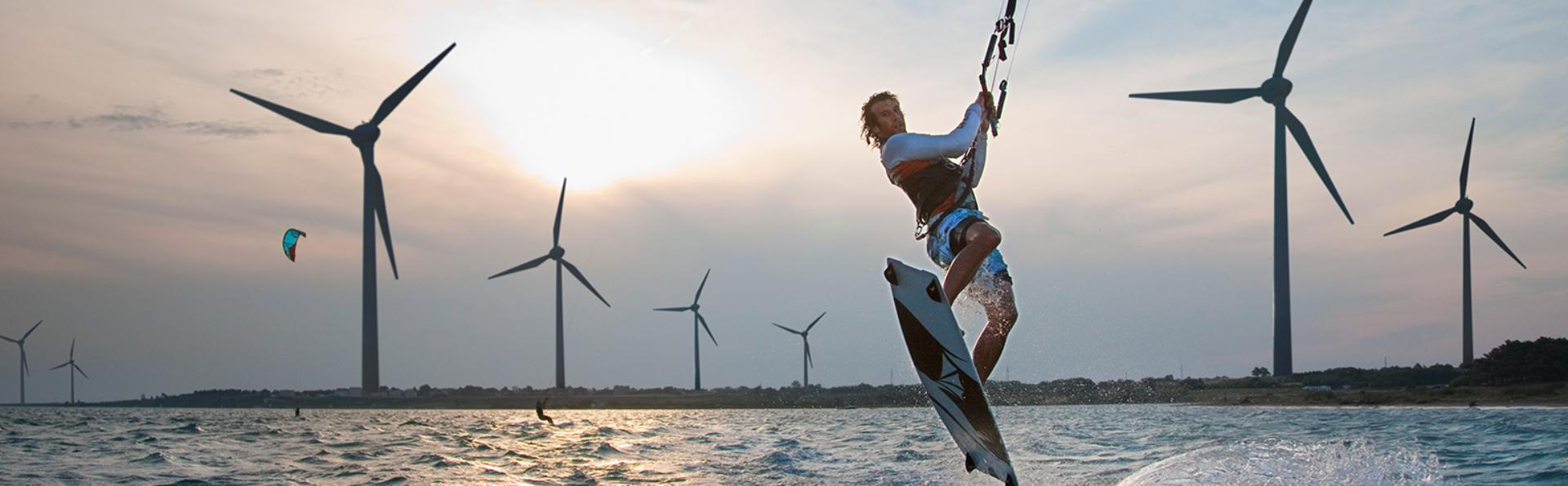 Croatia, Zadar, Kitesurfer jumping in front of wind turbine