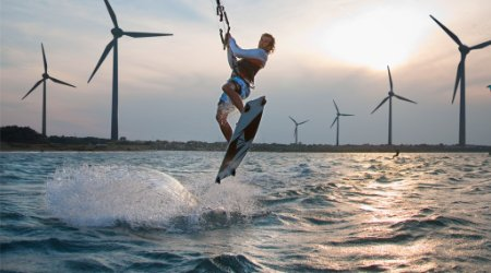 Kite-surfer catching air with wind turbines in the background