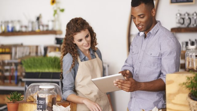 Small business retailers reviewing orders on a tablet