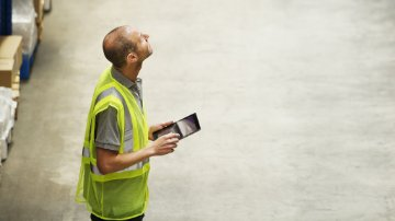 Manager using a digital tablet in a warehouse