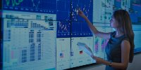 Businesswoman analyzing financial data on graphical screens