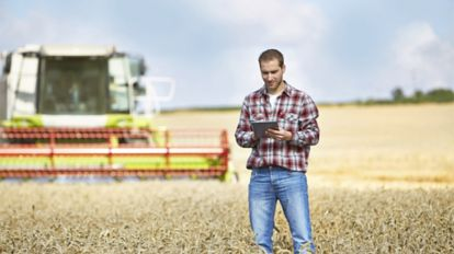 Photo of a farmer in a field using SAP Product Lifecycle Costing to review overhead costs on a tablet