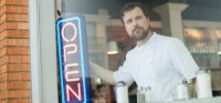 Small business owner standing by a neon open sign