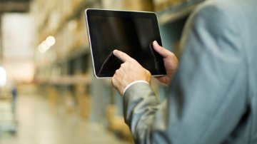Employee using an ipad to manage the extended supply chain