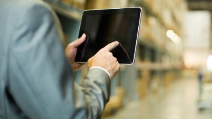 Image of a man in a warehouse using a mobile device
