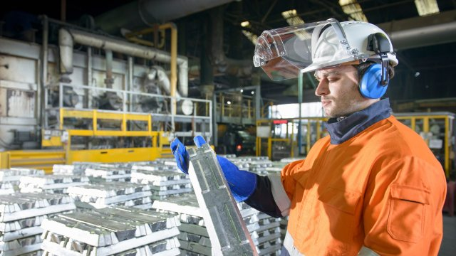 Worker in protective workwear inspecting zinc ingot in foundry