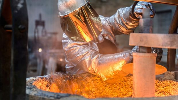 Image of a worker cleaning a molten metal flask in a foundry