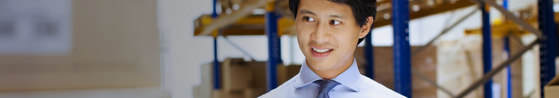Businessman standing in a warehouse reviewing the retail supply chain