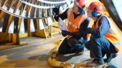 Two workers knee under a huge turbine shaft