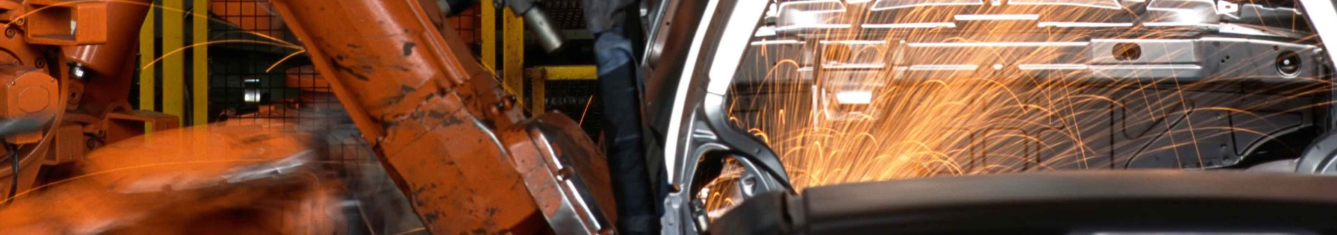 Sparks flying from welding machinery in a car manufacturing plant