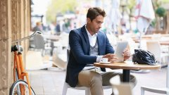 Man sitting at an outdoor cafe looking at a tablet