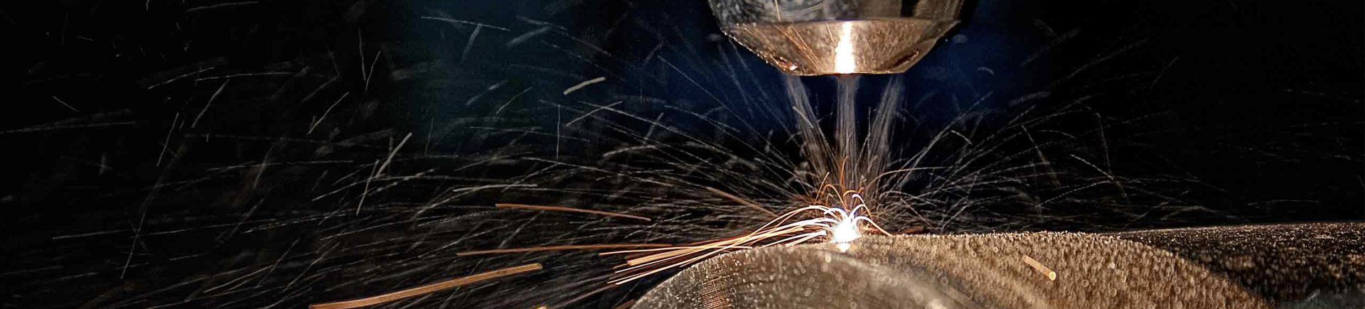 Sparks and metal splinters flying off industrial machinery components in a manufacturing plant using SAP software