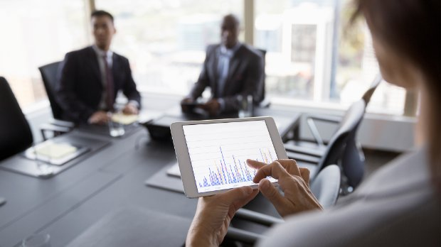 Businesswoman viewing bar chart on digital tablet in conference room meeting