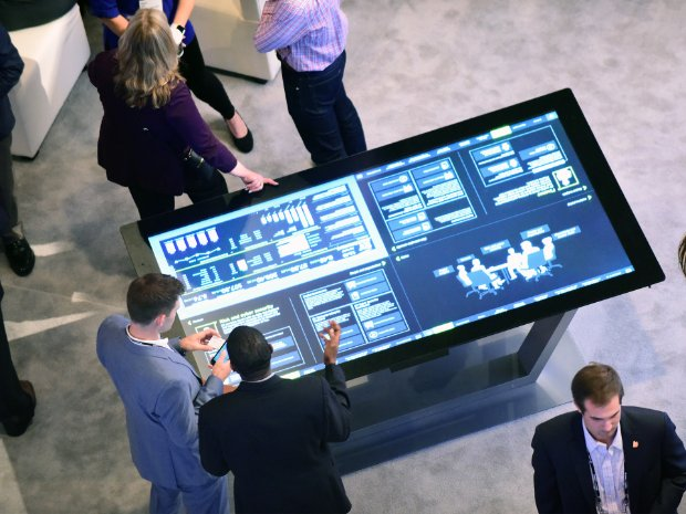 Image of professionals at an event discussing data on a touch screen monitor