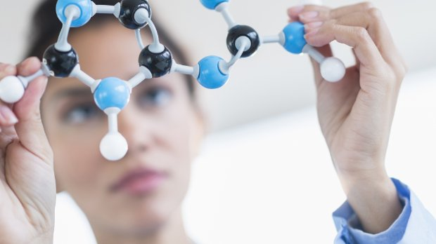 Photo of a scientist looking at molecular model