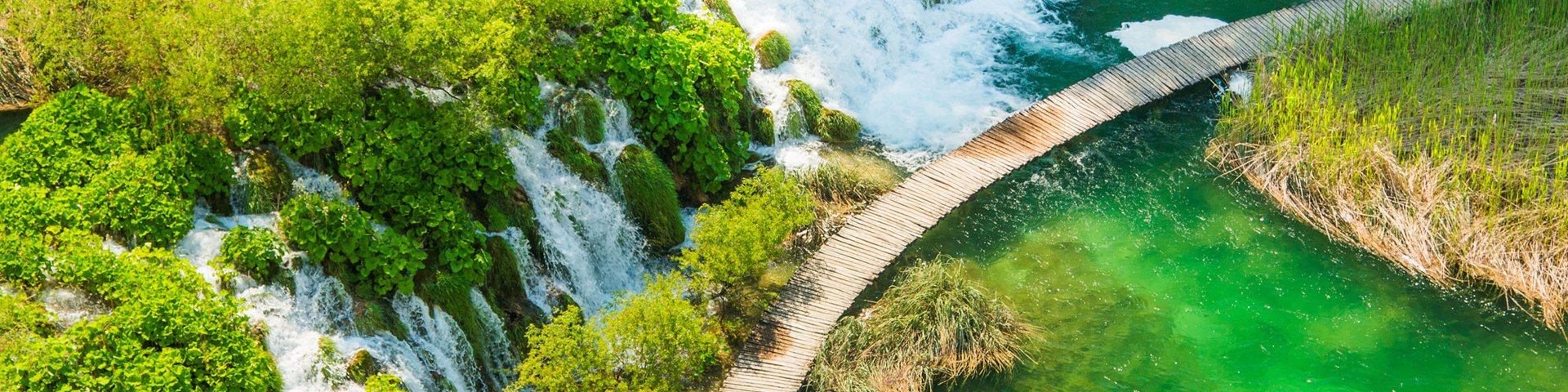 Beautiful waterfall, green water and wooden pathway