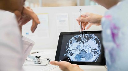 Photograph of doctors examining a scan on a tablet