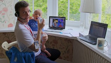 SAP employee working from home is bottle feeding his baby
